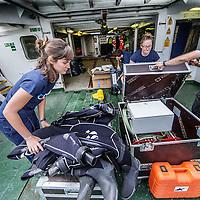 Nederland, Amsterdam, 7 juli 2016.<br /> Milieuclub Oceana ligt met haar onderzoeksschip Neptune in de Coenhaven van Amsterdam. Ze hebben geld gekregen van de postcodeloterij en gaan twee maanden op de Noordzee onderzoek doen hoe de visstand verbeterd zou kunnen worden.<br /> Op de foto: Het schip wordt klaargemaakt voor vertrek.<br /> Apparatuur wordt aan boord getakeld en geinstalleerd voor de wetenschappers aan boord van het schip. Duikpakken worden gesorteerd.<br /> <br /> Netherlands, Amsterdam, July 7, 2016.<br /> Environmental Club Oceana with her research vessel Neptune docked in the Coenhaven harbour of  Amsterdam. They have received money from the postcode lottery and will do research in the North Sea during two months to find out how fish stocks could be improved.<br /> On the photo: The ship is ready for departure.<br /> Equipment is hoisted aboard and installed for the scientists aboard the ship. Diving suits are sorted.<br /> <br /> Foto: Jean-Pierre Jans