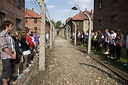 Students looking at each other from opposite sides of the fence - prisoners and guards. An exercise in empathy.Part of  The March of Remembrance and Hope in Auschwitz, Poland.