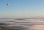 A hot air balloon glides over the early morning fog north of Cairns.