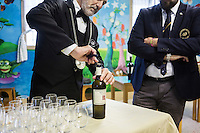 LECCE, ITALY - 10 NOVEMBER 2016: Roberto Giannone, a trained sommelier, opens a bottle of Chardonnay wine during a lecture to female inmates on the arts and crafts of wine tasting and serving, in the largest penitentiary in the southern Italian region of Apulia, holding 1,004 inmates in the outskirts of Lecce, Italy, on November 10th 2016.<br /> <br /> Here a group of ten high-security female inmates and aspiring sommeliers , some of which are married to mafia mobsters or have been convicted for criminal association (crimes carrying up to to decades of jail time), are taking a course of eight lessons to learn how to taste, choose and serve local wines.<br /> <br /> The classes are part of a wide-ranging educational program to teach inmates new professional skills, as well as help them develop a bond with the region they live in.<br /> <br /> Since the 1970s, Italian norms have been providing for reeducation and a personalized approach to detention. However, the lack of funds to rehabilitate inmates, alongside the chronic overcrowding of Italian prisons, have created a reality of thousands of incarcerated men and women with little to do all day long. Especially those with a serious criminal record, experts said, need dedicated therapy and professionals who can help them.
