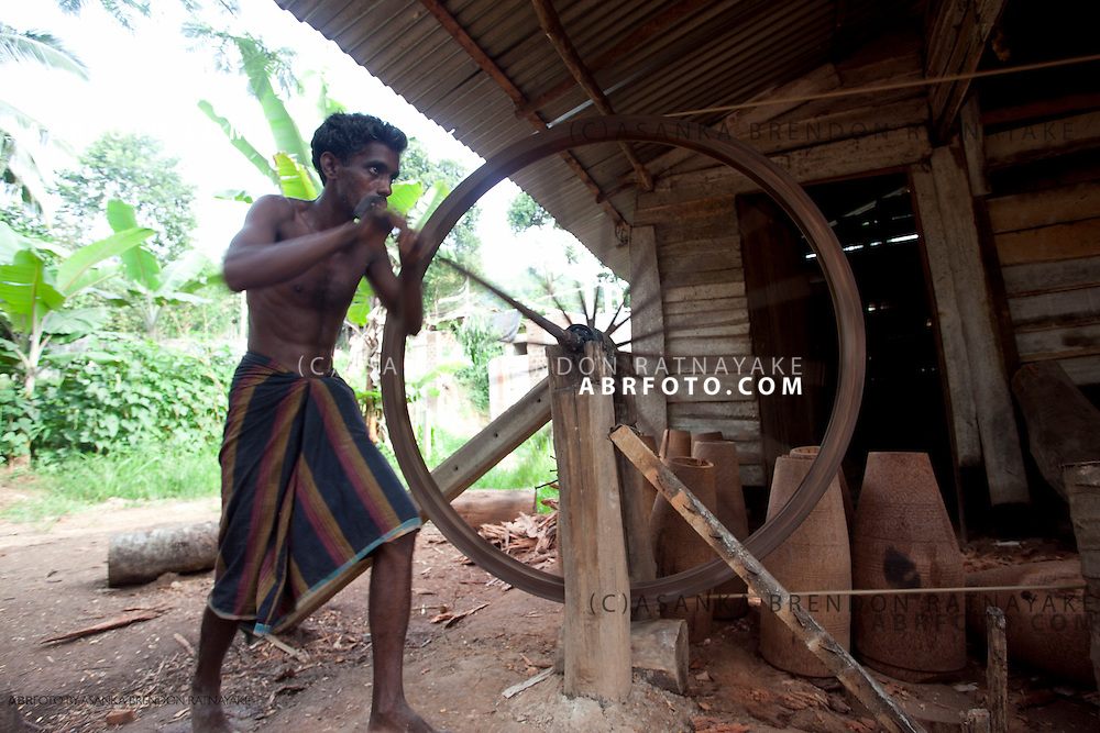 Craftsmen pushing the wheel of the manual wooden lathe.