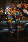 New York, NY, October 31, 2013. A performer in stilts seated on the roof a a truck waiting to take his place in the Greenwich Village Halloween Parade.
