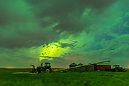 The great aurora display of May 27/28, 2017, here with a bright curtain shining though clouds over a farm tractor and implements near home in southern Alberta. The clouds and ground are lit green from the aurora.