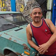 A local resident of Old Havana leans on vintage Soviet auto. Havana, Cuba.