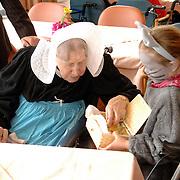 NLD/Huizen/20060310 - Westland Kaas Huizen bestaat 70 jaar en kinderen verkleed als muizen delen stukjes kaas uit aan bejaarden in het Vooranker Huizen
