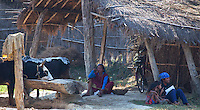 Woman and children sitting outside a traditional straw house, Bardiya, Nepal