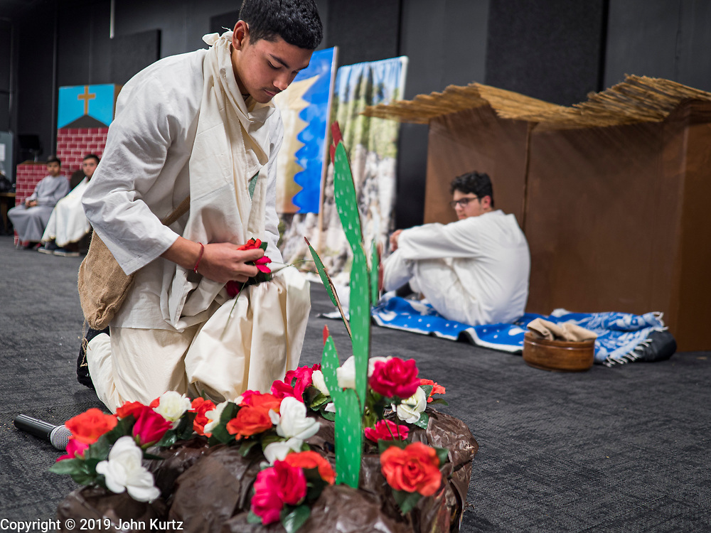 11 DECEMBER 2019 - DES MOINES, IOWA: A teenager playing Juan Diego gathers roses to present to the Virgin of Guadalupe during the Virgin of Guadalupe celebration at Our Lady of the Americas Catholic Church in Des Moines. Virgin of Guadalupe Day is one of the most important holy days in Mexican Catholicism. It marks Dec. 12, 1531, the day Juan Diego, an indigenous Mexican peasant, saw an apparition of the Virgin Mary on a barren hillside in what is now Mexico City. A basilica was built on the site. Virgin of Guadalupe Day is celebrated throughout Mexico and in Mexican communities in the United States.                PHOTO BY JACK KURTZ