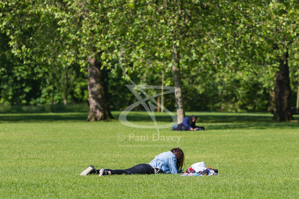 Green Park, London, June 6th 2016. A woman basks in the morning sunshine in Green Park as weather forecasters predict temperatures for London to be in the mid-twenties.