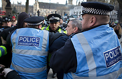 © Licensed to London News Pictures. 05/12/2016. London, UK. Police surround a man involved in a scuffle between pro and anti Brexit groups outside the Supreme Court in Westminster, London on the first day of a Supreme Court hearing to appeal against a November 3 High Court ruling that Article 50 cannot be triggered without a vote in Parliament. Photo credit: Peter Macdiarmid/LNP