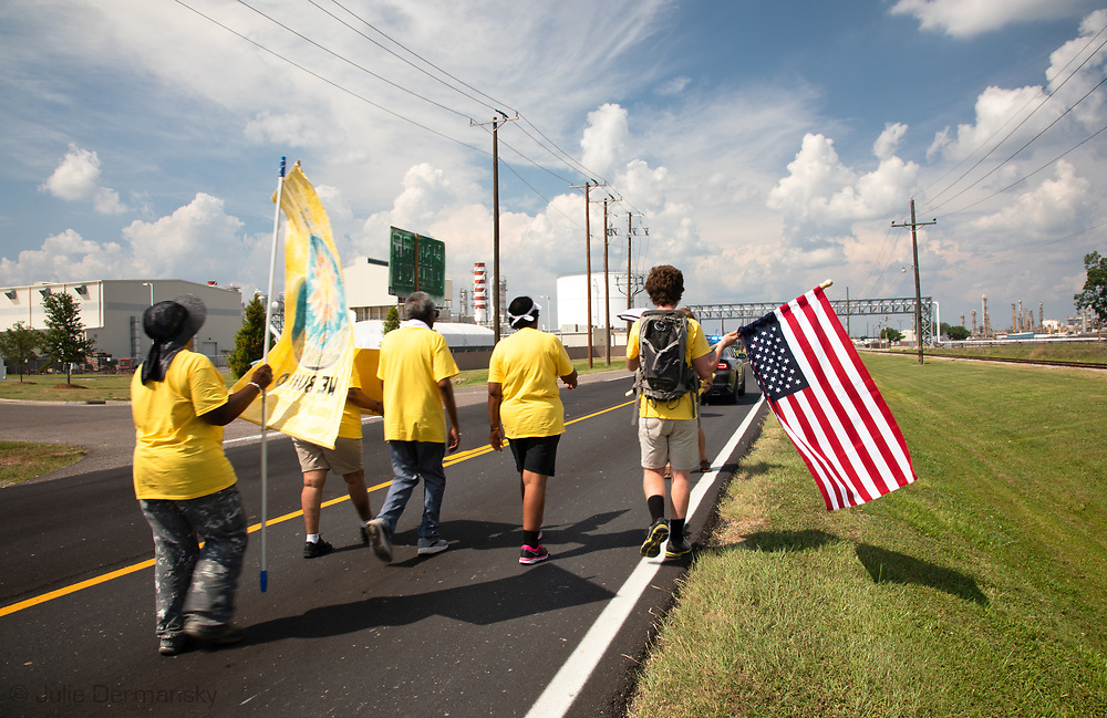 """Members of the Coalition against Death Alley and supporters  march by petrochemcial plants in Geismar, Louisiana aon the third day of a five day march through Louisiana's 'Cancer Alley' held by the Coalition Against Death Alley after being denied permits to march over river crossings. The Coalition Against Death Alley (CADA), is a group of Louisiana-based residents and members of various local and state organizations, is calling for a stop to the construction of new petrochemical plants and the passing of stricter regulations on existing industry in the area that include the groups RISE St. James, Justice and Beyond, the Louisiana Bucket Brigade, 350 New Orleans, and the Concerned Citizens of St. John.  Louisiana's Cancer Alley, an 80-mile stretch along the Mississippi River, is also known as the """"Petrochemical Corridor,"""" where there are over 100 petrochemical plants and refineries ."""