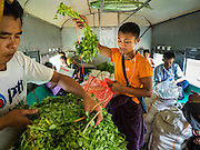 26 OCTOBER 2015 - YANGON, MYANMAR: Men sort vegetables they are taking to Yangon on the Yangon Circular Train. The Yangon Circular Railway is the local commuter rail network that serves the Yangon metropolitan area. Operated by Myanmar Railways, the 45.9-kilometre (28.5 mi) 39-station loop system connects satellite towns and suburban areas to the city. The railway has about 200 coaches, runs 20 times daily and sells 100,000 to 150,000 tickets daily. The loop, which takes about three hours to complete, is a popular for tourists to see a cross section of life in Yangon. The trains run from 3:45 am to 10:15 pm daily. The cost of a ticket for a distance of 15 miles is ten kyats (~nine US cents), and for over 15 miles is twenty kyats (~18 US cents).     PHOTO BY JACK KURTZ