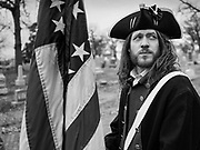 14 DECEMBER 2019 - DES MOINES, IOWA: MIKE ROWLEY, from Des Moines, wearing the uniform of the Revolutionary War Continental Army, holds an American flag before volunteers placed Christmas wreaths on veterans' headstones. Volunteers working with Wreaths Across America placed Christmas wreaths on the headstones of more than 600 US military veterans in Woodland Cemetery in Des Moines. The cemetery, one of the first in Des Moines, has the graves of veterans going back to the War of 1812.      PHOTO BY JACK KURTZ