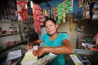 Ibu Hamriani inside her small kiosk at the Jongaya leprosy settlement, Makassar, Sulawesi, Indonesia. Ibu Hamriani, 39, moved to the Jongaya leprosy settlement 13 years ago.  She discovered she had leprosy much earlier but left the infection untreated until too late and now has problems with her toes and fingers.  She is married to Bapak Agus, 43, and they have one daughter together, Nurlina, 11, who was born in the house where she now runs a small kiosk selling general goods.