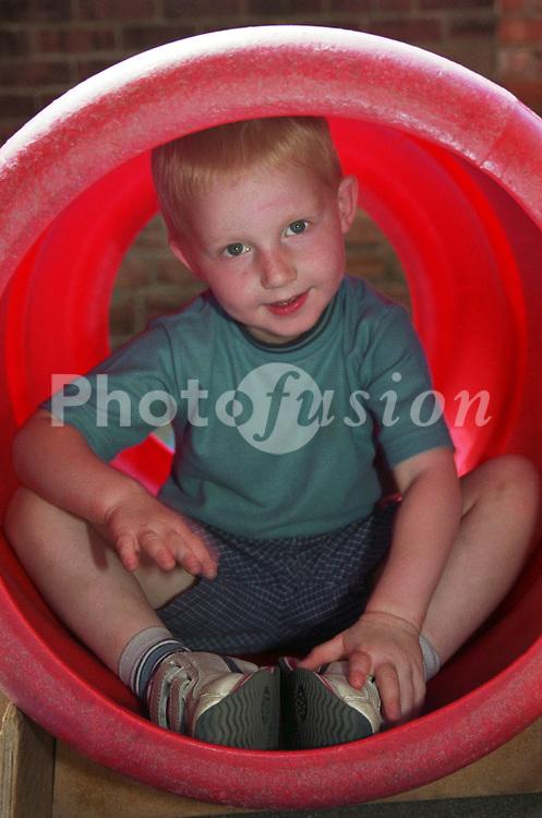 Nursery school boy sitting in plastic tube in playground smiling,