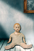 an old doll sitting in a shabby room