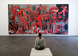 Woman looking at painting by AR Penck at Kuppersmuhle Museum in Duisburg Germany