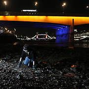 A mudlarker uses a torch to look for items under London Bridge on the bank of the river Thames in London, Britain June 06, 2016. When the river Thames is at low tide, mudlarkers scour the shore for historical artefacts and remains from there City of London's ancient past. Finds can date back to Roman times to when the city was found up until more recent times. Anyone can walk along the river and look for finds, but the uses of metal detectors and digging is restricted. Mudlarkers need to be licences by the Port of London Authority. All find should be register with the Museum of London. REUTERS/Neil Hall