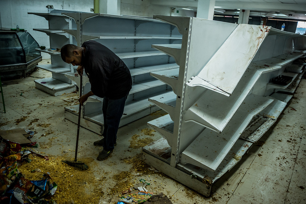 CARACAS, VENEZUELA - APRIL 21, 2017:  José Prada  works to clean the Ofercenter supermarket where he works, that was one of over a dozen stores looted late last night in El Valle, a working class neighborhood in Caracas. The streets of Caracas erupted into a night of riots, looting and clashes with National Guardsmen as anger from two days of pro-democracy protests spilled into unrest in working class neighborhoods and slums. Shots rang out throughout the night in El Valle, a neighborhood of mixed loyalties, as armored vehicles struggled to contain crowds of looters. At one point during the night, clashes became so heavy that a nearby children's hospital was evacuated after the ward filled with tear gas. The government said they were responding to an attack on the hospital by opposition protestors.  PHOTO: Meridith Kohut