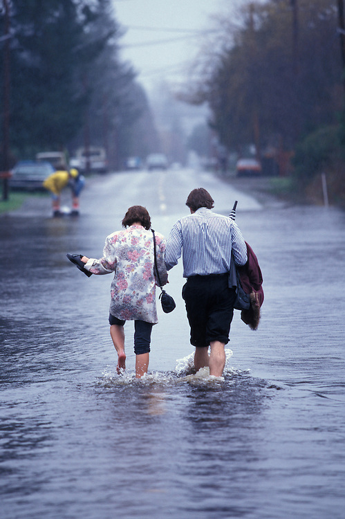 USA, Washington, North Bend, Couple walks through flooded streets during record early winter rains