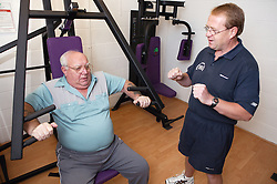 Access to services,  Fitness instructor and disabled man in the gym; using Chest Press,