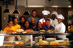 Stock photo of a chef and cooks standing with other restaurant employees showcasing their freshly cooked food