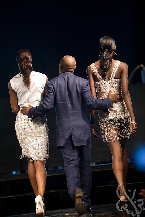 """Acclaimed fashion designer Chris Aire is escorted out onto the runway by Nigerian model Oluchi (r) during his show in support of the July 13, 2008 leg of the ThisDay music and fashion festival in Lagos, Nigeria. The festival, themed """"Africa Rising"""", aims to raise awareness of African issues while promoting positive images of Africa using music, fashion and culture in a series of concerts and events in Nigeria, the United States and the United Kingdom. ."""
