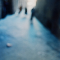 Three blurred figures on a street in Rome, Italy