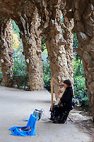 A local busker plays the harp beside the former home of Antoni Gaudi within the walls of Park Guell, Barcelona, Spain