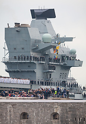 © Licensed to London News Pictures. 16/08/2017. Portsmouth, UK.  The Royal Navy's new aircraft carrier HMS Queen Elizabeth towers above the round tower at Portsmouth Harbour entrance as she arrives for the first time. Thousands of people lined the shores of Portsmouth and Southsea to welcome the Royal Navy's newest and largest ever ship into her home port. Photo credit: Rob Arnold/LNP
