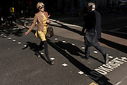 Pedestrian commuters cross a busy street in summer sunshine in central London with a 'Look Right' safety message stencilled on the asphalt.