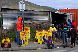 Residents of the township sit by posters promoting the COPE political party  in Masiphumelele near Fish Hoek, Cape Town during the 2016 local government elections held across South Africa on the 3rd August 2016<br /> <br /> Photo by - Ron Gaunt / RealTime Images
