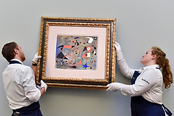 "© Licensed to London News Pictures. 15/06/2017. London, UK. Technicians hang ""Femme et oiseaux"", 1940, by Joan Miró (estimate on request).  Preview of Impressionist and Modern art sale, which will take place at Sotheby's New Bond Street on 21 June.  Photo credit : Stephen Chung/LNP"