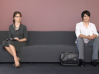 Business man and woman sitting on sofa