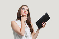 Pensive young woman holding tablet PC over gray background