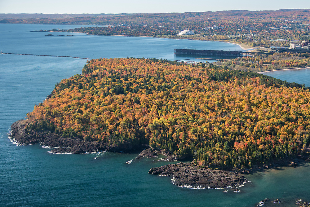 Aerial photography of Presque Isle Park in Marquette, Michigan showing the park's Black Rocks area and Lake Superior during fall color season.