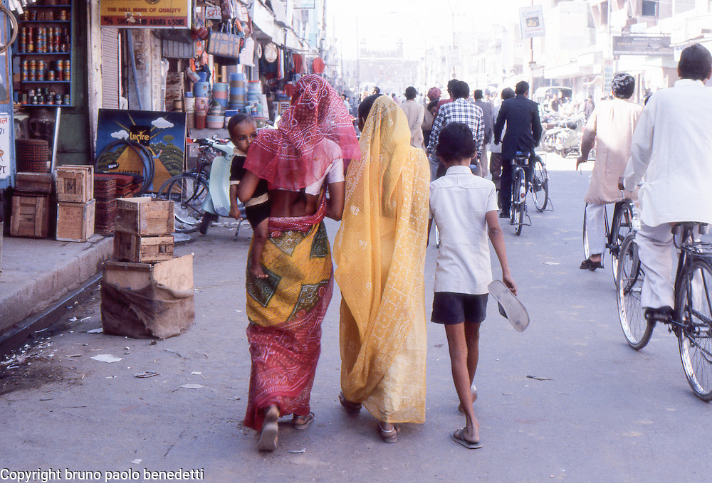 walking indian women in sari with kids along shops in indian town street view from behind