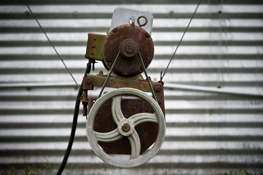 Electric motor pulley rig system for wiring on a farm in front of aluminum siding of a silo