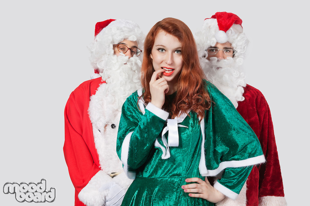 Portrait of young men in Santa costume standing with woman against gray background