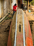11 MARCH 2016 - LUANG PRABANG, LAOS:  A man repairs a small canoe in front of his home in the community of Chomphet, across the Mekong River from Luang Prabang. Laos is one of the poorest countries in Southeast Asia. Tourism and hydroelectric dams along the rivers that run through the country are driving the legal economy.      PHOTO BY JACK KURTZ