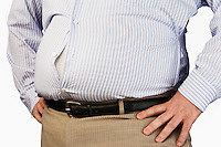 Overweight Man standing with unbuttoned shirt hands on hip mid section