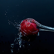 High-speed shot of water hitting a red delicious apple in studio.