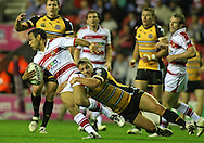 Wigan - Sunday 20th September 2009:Amos Roberts of the Wigan Warriors is tackled by Kirk Netherton of the Castleford Tigers  during the Engage Super League Elimination Playoff match between The Wigan Warriors & The Castleford Tigers at the DW Stadium in Wigan. (Pic by Steven Price/Focus Images)