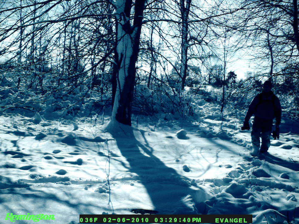 Zach Johnson walking into his blind for a late season deer hunt is captured on a trail camera.  Note the bow in one hand and camera in the other.