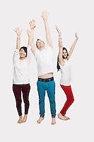 Multi-ethnic friends in casuals with arms raised standing together over white background