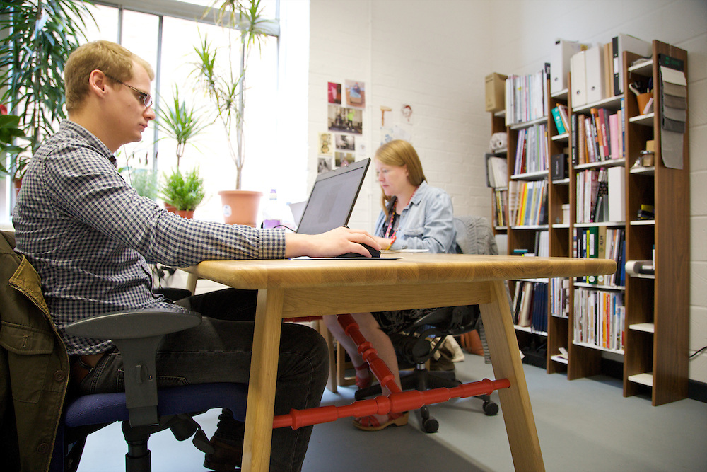 Furniture designer Leonhard Pfeifer's Hackney studio, London. David Broad (left) and Karla Thompson (right) wokring on the Affoltern dining table, Manufactured by Romania producer DoroBanti. The Harlesden library shelves sit on the wall behind them, manufactured in Estonia by Woodman<br /> CREDIT: Vanessa Berberian for The Wall Street Journal<br /> GURU-Pfeifer