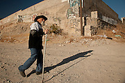 An elderly man walks his dog past a gang marker in memory of a slain member along a street corner where ten people have been killed in drug crimes in Juarez, Mexico January 15, 2009. The ongoing drug war has already claimed more than 40 people since the start of the year. More than 1600 people were killed in Juarez in 2008, making Juarez the most violent city in Mexico.    (Photo by Richard Ellis)