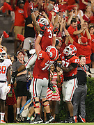 Georgia Bulldogs running back Todd Gurley (3) is lifted by Georgia Bulldogs offensive tackle John Theus (71) after Gurley scored a touchdown during Saturday's college football game against the Clemson Tigers Sanford Stadium in Athens. (Staff Photo: David Welker)