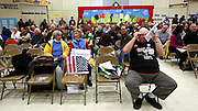 Wearing a 'Guess We Can't' tee-shirt, David Robertiello of Portland, right, adjusts his glasses, to read handout literature given to him at the Portland, ME, caucus held at the Riverton School, Saturday, Feb. 11, 2012 . (Cheryl Senter for the New York Times)