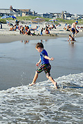 Boy plays with sand at the waters edge, Ocean City, New Jersey, USA