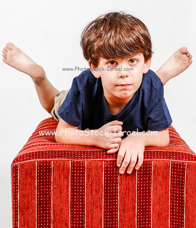 Young boy of six relaxes indoors Model released